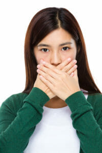 Image of a young woman hiding her teeth for the dark spots on teeth blog post.
